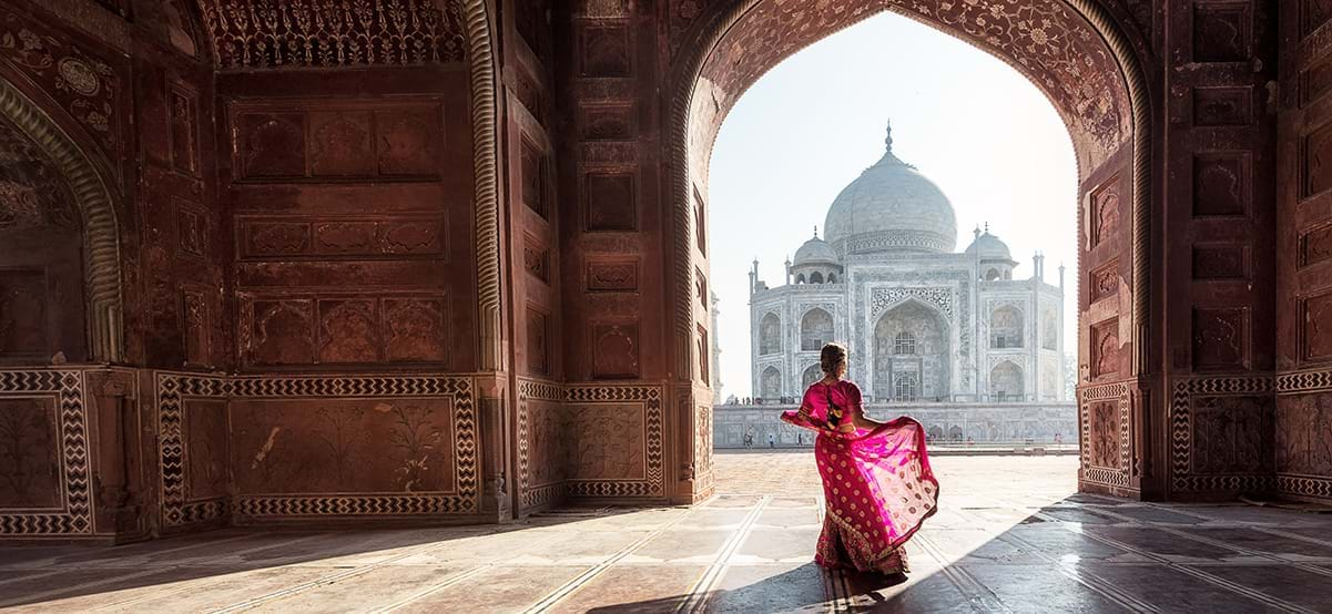 Woman in red Saree gown dancing in front of the Taj Mahal India during luxury culinary and culture vacation