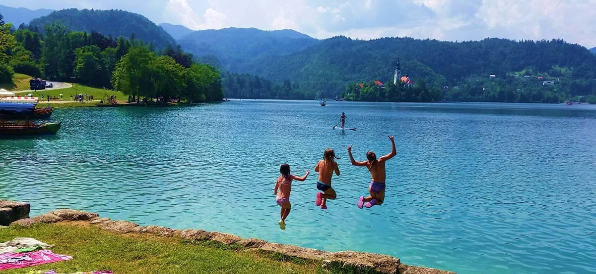 View of kids jumping into Lake Bled during luxury family vacation to Slovenia